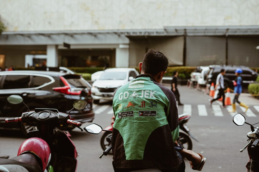 A Go-Jek rider waiting for his passenger. Go-Jek is a bike taxi app popular in Indonesia.