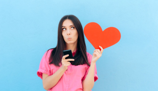 A young lady holding smartphone and a heart in her hands and thinking about dating apps