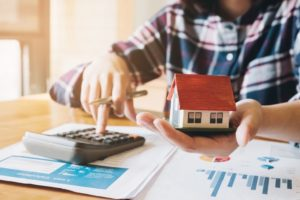 A man using a calculator to calculate budget for his dream house